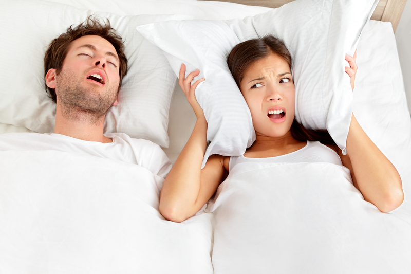 Man snoring in bed and keeping his wife awake